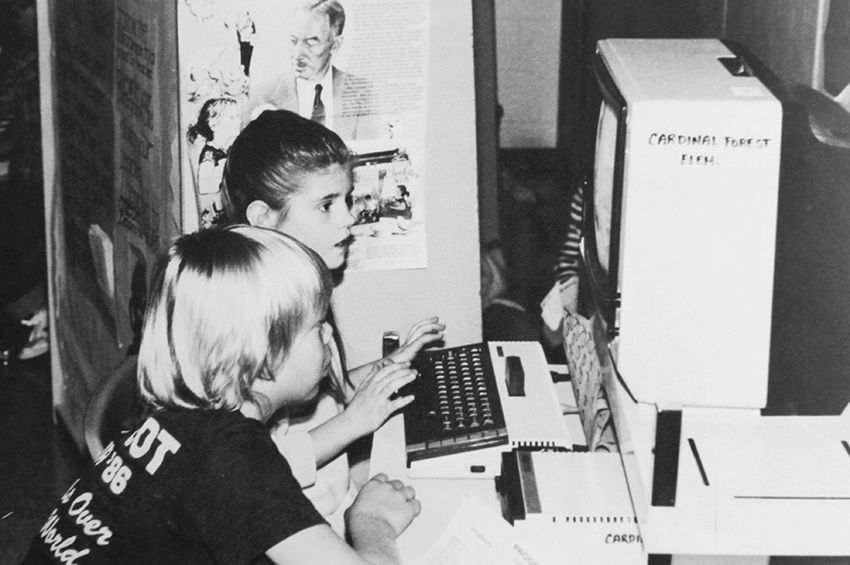 Black and white photograph of two students sitting at a computer workstation.