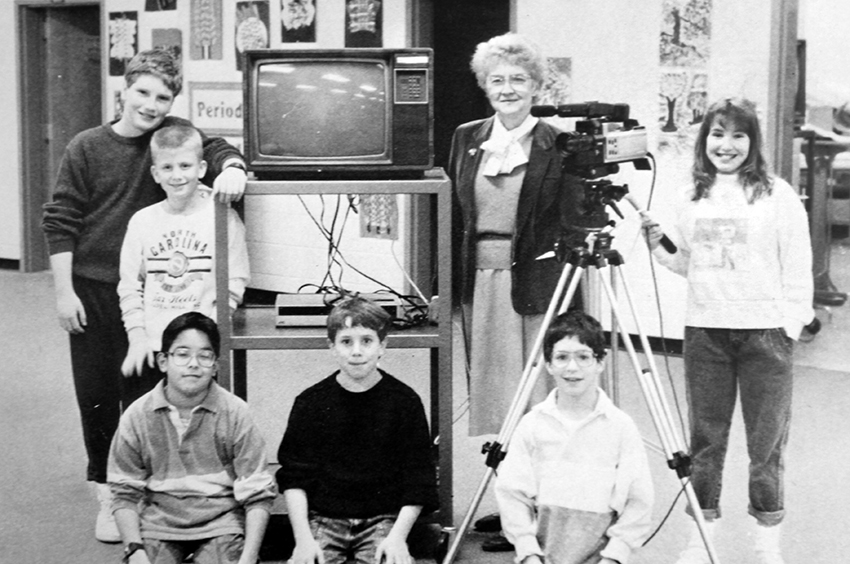 Black and white photograph of Cardinal Forest's broadcast television news team, taken in 1988. Six children and one adult are pictured. They are standing next to a television and VCR on a portable cart, and a small video camera on a tripod.