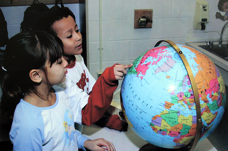 Photograph of two students looking at a globe.